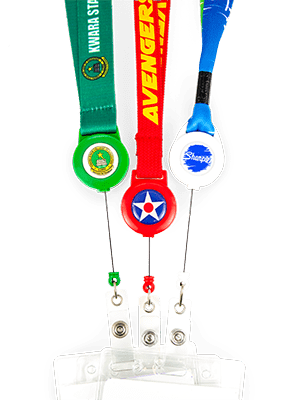 Green, red, and blue lanyards, with matching badge reels, partially extended, attached to badges