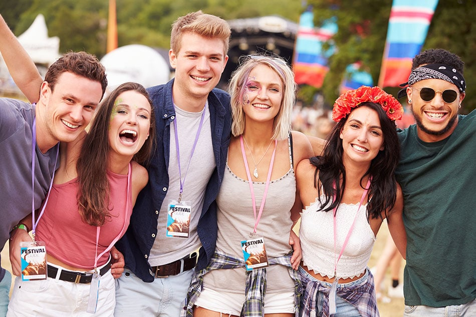Happy young people at an outdoor festival, wearing lanyards with badges