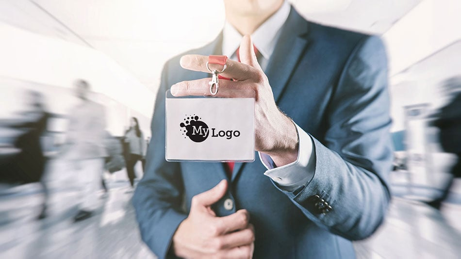Business professional holding up lanyard with a badge displaying a corporate logo